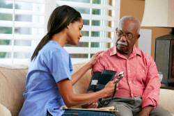 caregiver checking the blood pressure of the old man