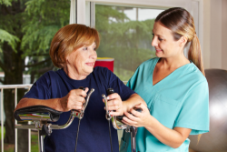 elderly woman having a physical therapy assisted by a caregiver